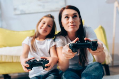 KYIV, UKRAINE - OCTOBER 19, 2020: Positive mother and daughter playing with joysticks at home on blurred background