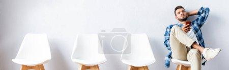 Hombre joven usando teléfono inteligente mientras está sentado en la silla en el pasillo, pancarta