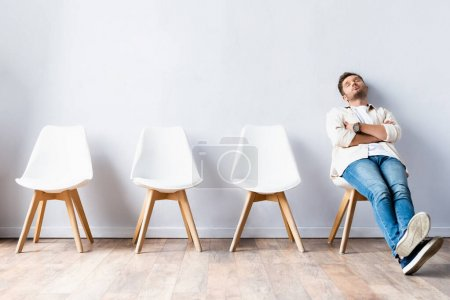 Photo for Tired man sitting with crossed arms near chairs in hall - Royalty Free Image