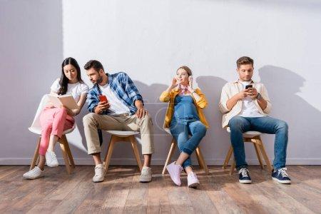 Personas multiculturales y mujeres embarazadas usando teléfonos inteligentes y leyendo libros sobre sillas en cola
