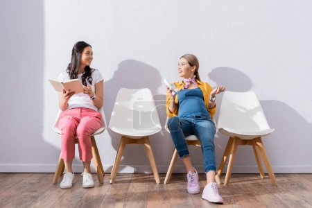 Photo pour Sourire femme enceinte tenant écouteurs près de femme asiatique avec livre en file d'attente - image libre de droit