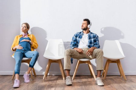 Photo pour Homme en casque assis près de la femme enceinte en file d'attente - image libre de droit