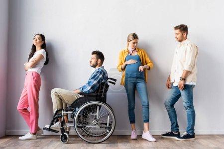 Photo pour Femme enceinte vérifiant le temps près de l'homme handicapé et les personnes multiethniques dans le hall - image libre de droit