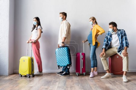Multiethnic people in medical masks waiting with suitcases in airport
