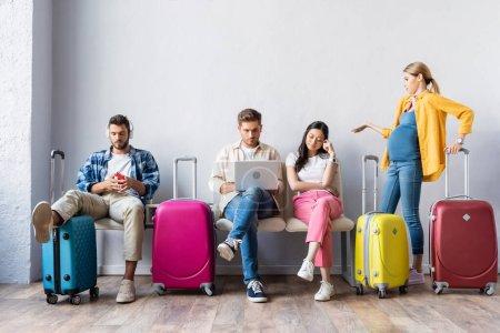 Photo pour Femme enceinte pointant de la main près des personnes multiethniques avec des appareils et des valises à l'aéroport - image libre de droit