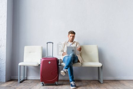 Man using smartphone near suitcase in airport