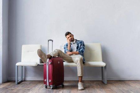 Photo pour Homme fatigué dans les écouteurs assis près de la valise en attendant dans le hall de l'aéroport - image libre de droit