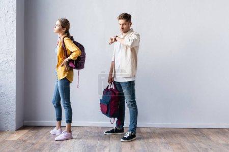 Photo pour Temps de contrôle étudiant sur montre-bracelet près de la femme avec sac à dos dans le hall - image libre de droit