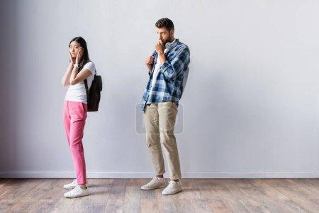 Photo pour Inquiet asiatique étudiant debout près de l'homme dans hall avant examen - image libre de droit