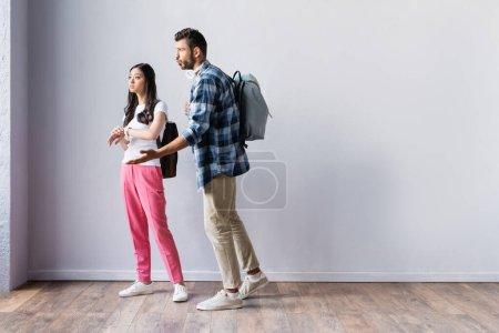 Photo pour Étudiants multiethniques avec des sacs à dos regardant loin tout en se tenant dans le hall avant l'examen - image libre de droit