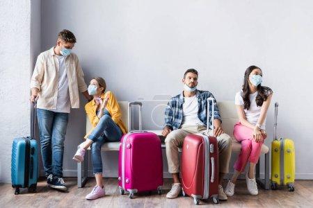Personas multiculturales en máscaras médicas esperando cerca de maletas en el aeropuerto