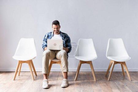 Photo pour Homme positif travaillant sur ordinateur portable près des chaises dans le hall - image libre de droit