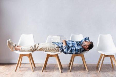 Photo pour Homme en tenue décontractée allongé sur des chaises en attendant dans le hall - image libre de droit