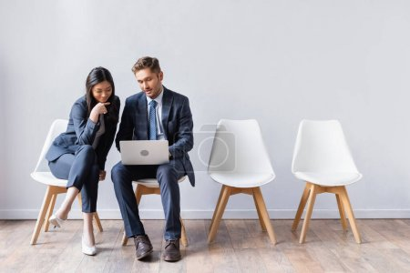 Smiling asian businesswoman sitting near businessman with laptop before job interview