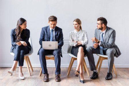 Multiethnic businesspeople looking at businessman with laptop before job interview in office