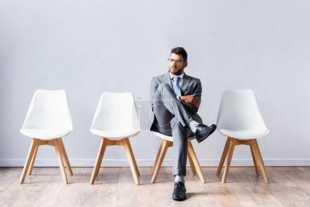 Young businessman sitting with crossed legs on chair in office