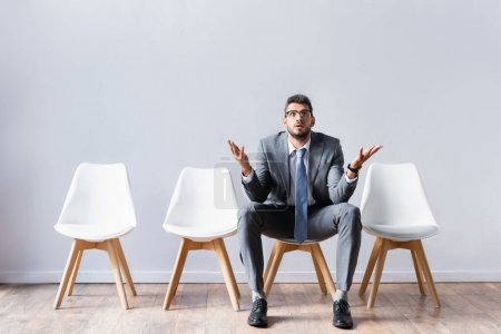 Businessman in suit pointing with hands while waiting job interview in office