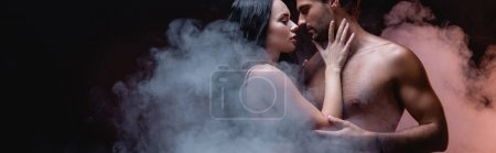 sexy woman touching shirtless man while standing face to face on black background with smoke, banner