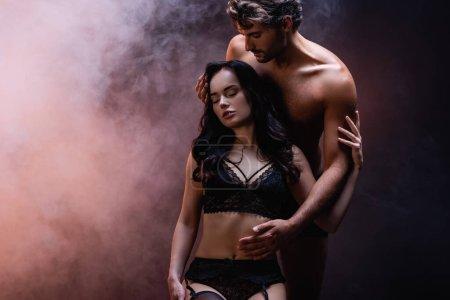 Photo pour Sexy homme torse nu toucher femme séduisante en dentelle noire sous-vêtements sur fond sombre avec de la fumée - image libre de droit