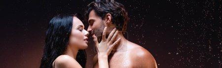 Photo pour Vue latérale de femme sexy près de jeune homme torse nu sous la pluie sur fond sombre, bannière - image libre de droit