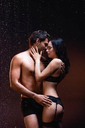 Photo pour Sexy homme torse nu embrassant femme séduisante en lingerie noire et bas sur fond sombre - image libre de droit