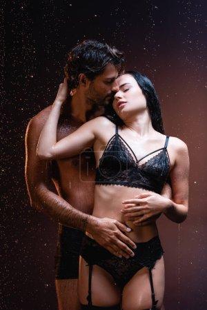 Photo pour Jeune homme étreignant femme séduisante en dentelle noire lingerie sous la pluie sur fond sombre - image libre de droit