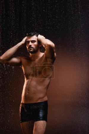 muscular shirtless man in black underpants touching head under rain on dark background