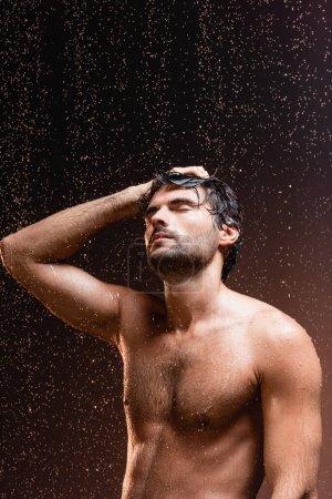 Photo pour Homme musclé torse nu avec les yeux fermés sous des gouttes de pluie tombantes sur fond sombre - image libre de droit