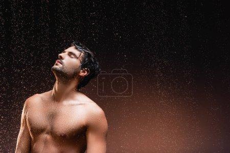 Photo pour Homme torse nu avec torse musclé debout sur fond sombre sous la pluie tombante - image libre de droit