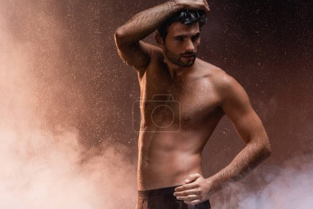 sexy shirtless man posing with hand on hip under rain on dark background with smoke