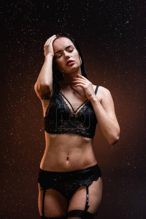 sexy woman in black lace underwear and stockings with closed eyes under falling raindrops on dark background