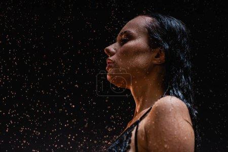 Photo pour Femme sensuelle et humide posant sous la pluie sur fond sombre - image libre de droit