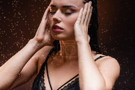 Photo pour Jeune femme en dentelle noire posant sous la pluie avec les yeux fermés sur fond sombre - image libre de droit