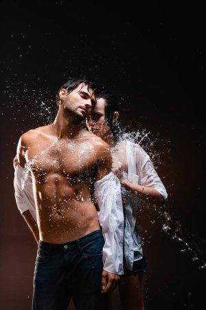 Photo pour Jeune femme déshabiller sexy, homme musclé près des éclaboussures d'eau sur fond sombre - image libre de droit