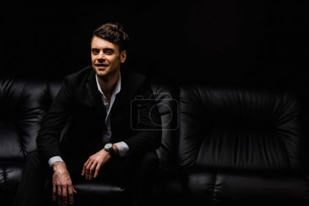 cheerful man in formal wear sitting on sofa isolated on black