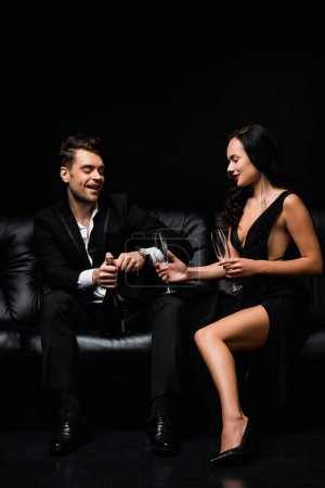 Photo for Cheerful man in suit holding bottle near sexy woman in dress with glasses isolated on black - Royalty Free Image