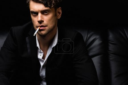 confident man in formal wear smoking cigarette and looking at camera isolated on black