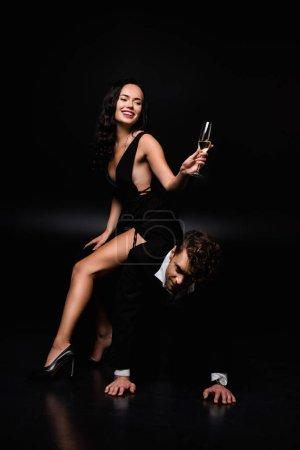 Photo pour Gaie femme dominante en robe assis de l'homme soumis et tenant un verre de champagne sur noir - image libre de droit