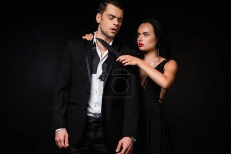 Gefährliche Frau im Kleid hält Messer am Hals des Mannes im Anzug isoliert auf schwarz