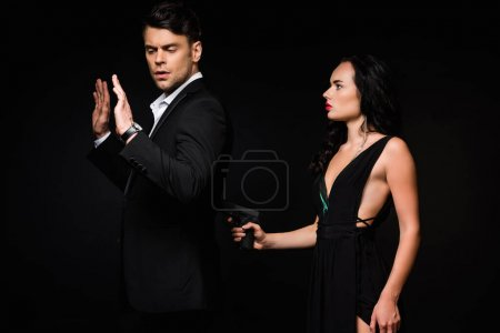 dangerous woman in dress holding gun while aiming in man isolated on black