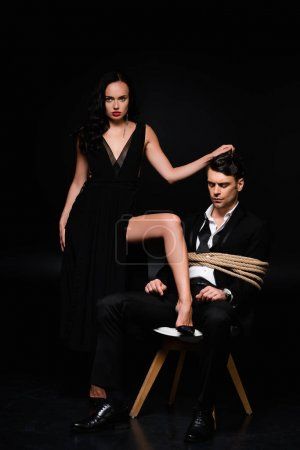full length of dominant woman in dress pulling hair of tied submissive man sitting on chair on black