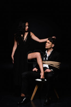 full length of dominant woman in dress pulling hair of tied submissive man in suit sitting on chair on black