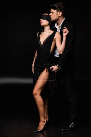 full length of blindfolded woman in dress standing with man in suit on black