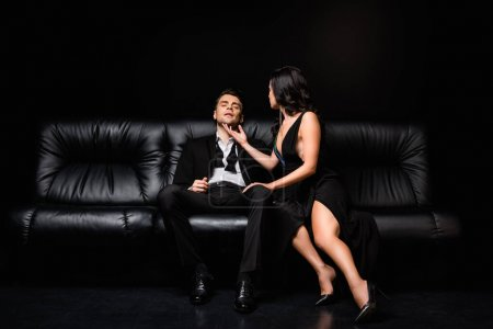 elegant woman in dress sitting on couch with man in suit on black