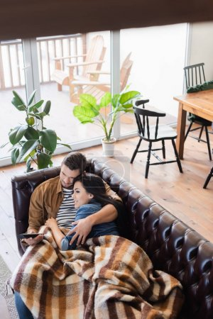 high angle view of young couple watching tv on leather couch under plaid blanket, blurred foreground