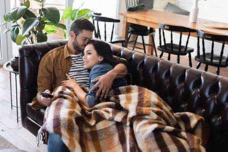 Photo pour Jeune homme avec les yeux fermés étreignant petite amie souriante regarder la télévision sur le canapé en cuir sous couverture à carreaux confortable - image libre de droit