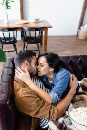 Photo for Young couple hugging and kissing on leather sofa near wooden table and chairs on blurred foreground - Royalty Free Image