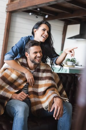 cheerful woman pointing with finger while hugging shoulder of man watching movie under checkered blanket