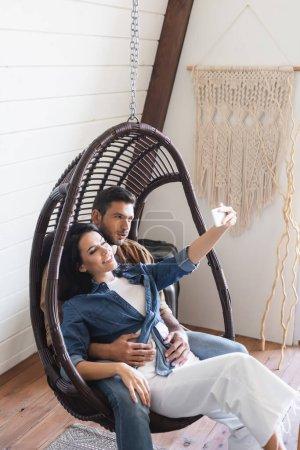 Photo pour Heureux jeune couple assis dans une chaise en rotin suspendu et prendre selfie sur téléphone mobile - image libre de droit