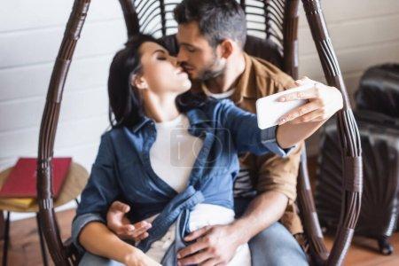 Photo pour Jeune femme prenant selfie sur smartphone tout en embrassant avec petit ami dans une chaise suspendue, fond flou - image libre de droit